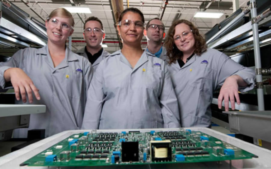 Five Melitron employees with safety glasses pose in front of a circuit board in Melitron's manufacturing facility.