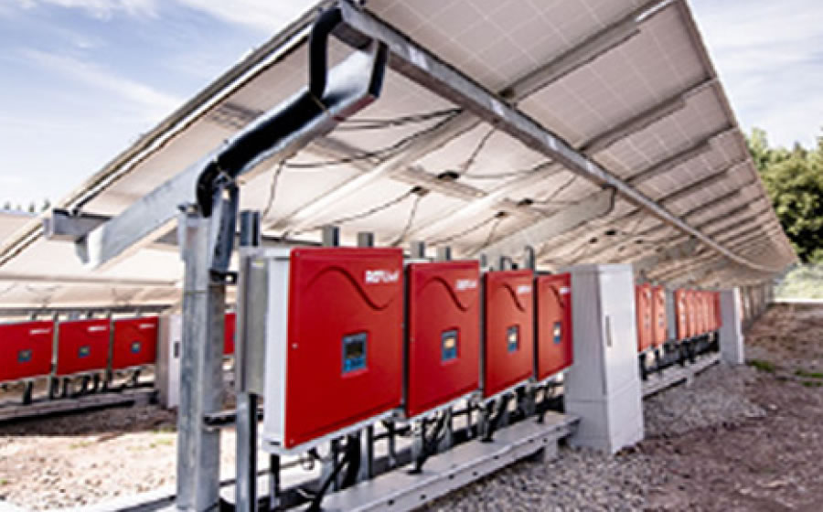 Melitron enclosure systems positioned underneath a series of solar panels.