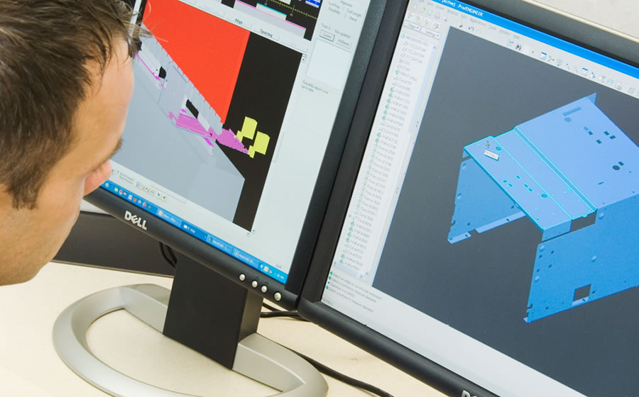A Melitron employee works on a CAD rendering on a desktop computer.