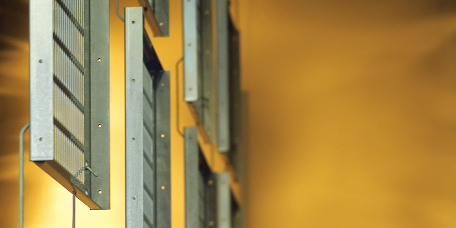 Hanging metal vent covers enter a powder coating finishing station.